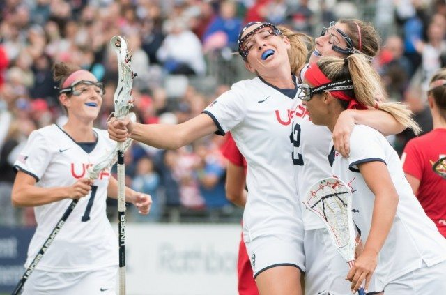 USA's Taylor Cummings(facing) celebrates with Kayla Treanor(12) and Alex Aust(nearest the camera) after Treanor had scored with an over- the shoulder shot at the 2017 FIL Rathbones Women's Lacrosse World Cup at Surrey Sports Park, Guilford, Surrey, UK, 15th July 2017